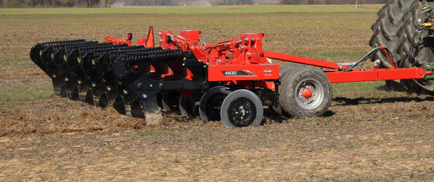 A side view of a KUHN Krause 4830 trailed in-line ripper working the ground.