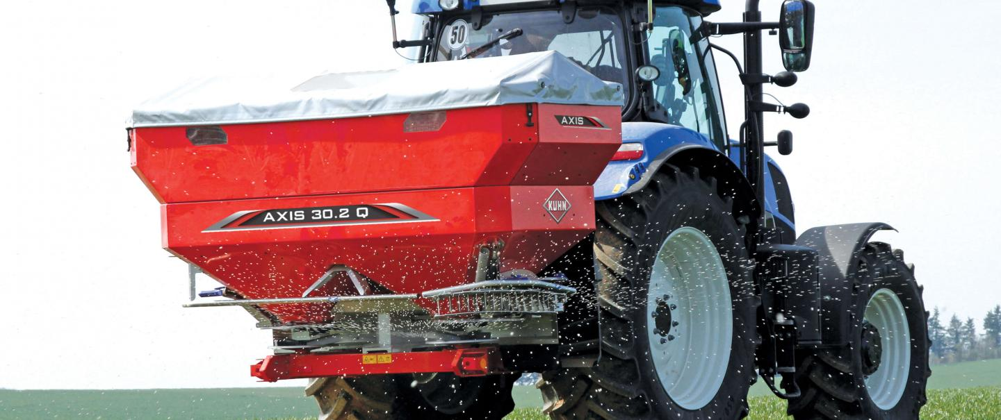 An Axis 30.2 Q fertilizer spreader quartering away in a field.
