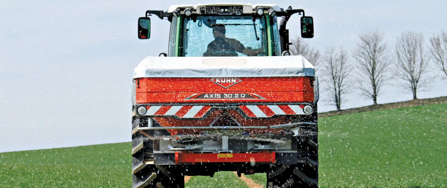 A rear view of an Axis 30.2 Q fertilizer spreader heading down the field spreading fertilizer.