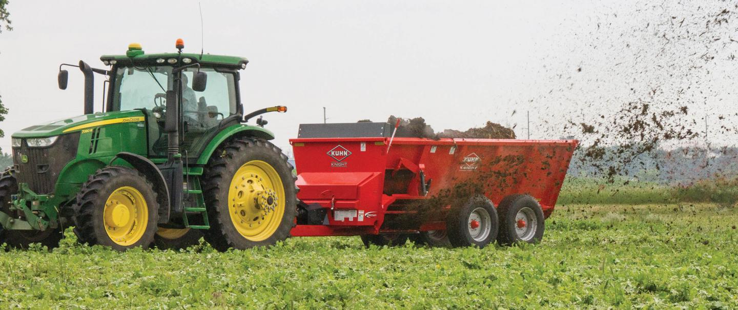 Side view of a SL 124 manure spreader spreading in a hay field.